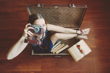 Young beautiful woman with retro camera sitting in big suitcase. Time to travel, luggage