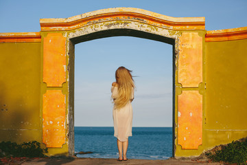 Pretty girl in white dress standing in old doorway into blue sea. Enjoying nature, desire to travel, blond fluttering hair