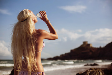 Fashion blond sporty woman in bikini drinking fresh clean water from the bottle. Hot summer day, activity outdoor, healthy lifestyle