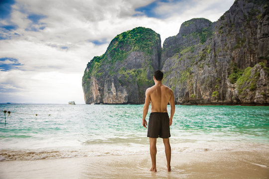 Full body shot from the back of a handsome young man standing on a beach in Phuket Island, Thailand, shirtless wearing boxer shorts, showing muscular fit body