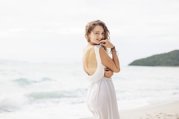 Portrait of happy girl in white dress with long hair on the beach. Summer vacation
