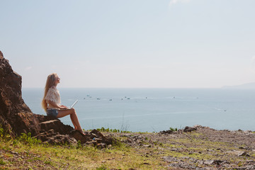 Young attractive woman sitting outdoor near beautiful ocean using laptop computer and enjoy freedom and summer vacation