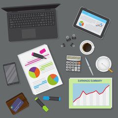 Top view of office dark desk background including laptop, digital devices, financial and business objects.