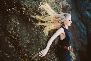 Art portrait of beautiful blond woman with long hair lying on big rocks