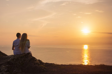 Young love couple sitting on the cliff and watching sunrise