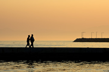 Grandpa and grandma on vacation walking on a pier by the sea at sunset in Chalkidiki, Greece