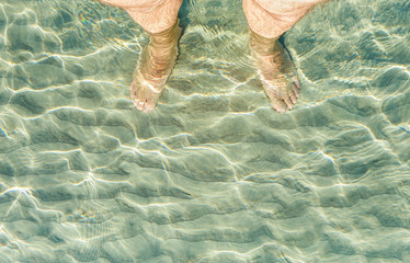 Man bare feet in crystal clean water near seashore