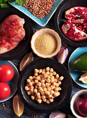 Ingredients of middle eastern cuisine - chickpeas, lentils, couscous, pomegranate, red onion, tomato, avocado,  chicken breast, paprika, parsley, olive oil and garlic.