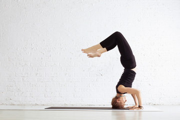 Young female doing yoga exercise headstand in studio. Individual Sport activity, relaxation