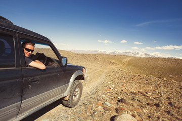 Happy travelling man sitting in car and driving on off-road mountain way