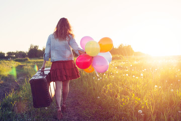 Young Woman walking with big suitcase and coloured balloons on meadow road. Sunrise, wild flowers, summer  vacation and travel