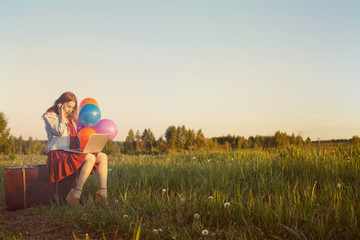 Young woman sitting on big suitcase on wild meadow with coloured balloons holding laptop. Travel guide, Buy Tickets, online shopping, enjoy freedom