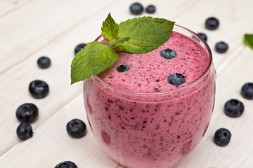 Blueberry smoothie in a glass on wooden table