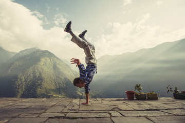 Young sporty man doing handstand exercise in beautiful mountain landscape. Sports outdoor lifestyle