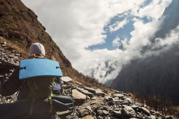 Girl with big backpack walking in high mountains. Trekking in Himalayas, Nepal