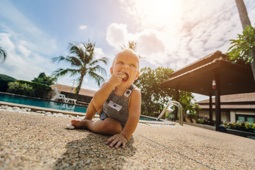 Funny baby boy trying to  eat stone outdoor near swimming pool. Summer vacation, sunny day, palm trees