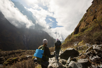 Girls with big backpack and trekking sticks walking in high mountains. Trekking in Himalayas, Nepal