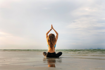 Young Girl sitting on sea shore in Lotus pose and practicing yoga