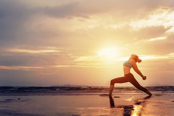 Silhouette of Yoga woman practicing standing yoga asana on sea shore on sunset