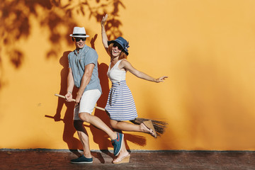 Cheerful traveling couple having fun jumping on a broom. Easy travel together. Orange colour background