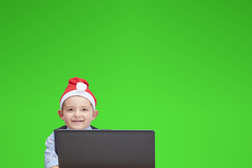 A child wearing in cap of Santa Claus looking at a laptop