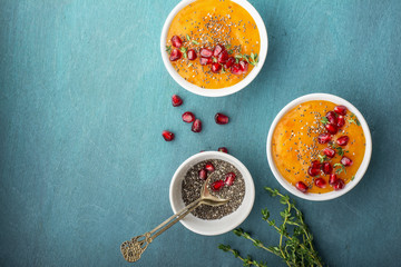 Detox orange healthy breakfast smoothies with seasonal ripe fruit, chia seeds, pomegranate  on a bright colored background. Top view. The concept of organic food.