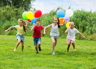 Children running with colorful balloons