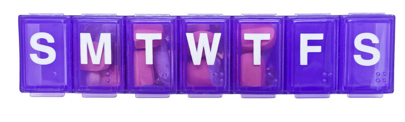Purple plastic daily meds container. Isolated.