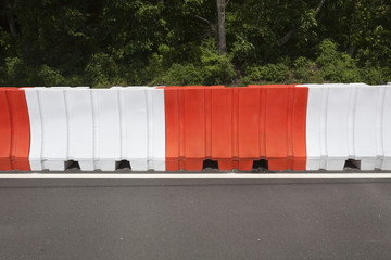 Orange and white traffic construction barricade.