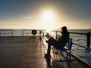 Hobby photograph sit on bench at camera on tripod. Wooden board quay