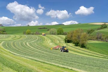 Photo sur Plexiglas Olive Zwei Traktoren bei der Ernte von Grünfutter in hügeliger Landschaft