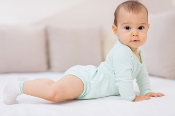 Baby girl on white bed / Cute baby girl lying on her tummy