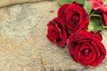 Red roses on stone table