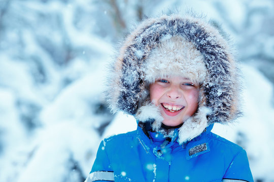 Cute little boy wearing warm clothes playing on winter forest