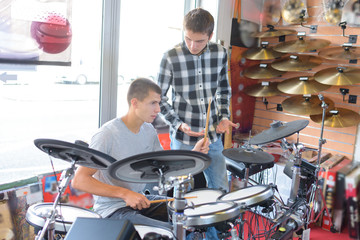 Young men looking at electronic drum kit