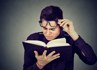man with eye glasses trying to read book has sight problems