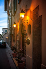 Classic cafe restaurant entrance illuminated by two vintage lantern in old italian town as seen from the lateral side - vintage look