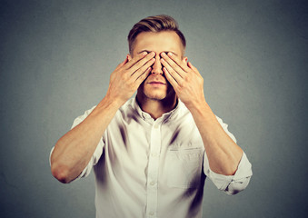 Young man covering eyes with both hands