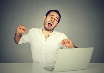 Sleepy worker with laptop computer yawning