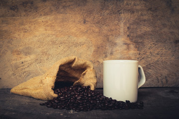 Cup of coffee sacks of coffee beans on the old wooden floor. Vin