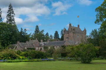 Cowdor, Scotland - June 2, 2012: The brown-gray stone structure of undamaged Cowdor Castle under blue sky. Flag on top. Large part of formal garden in forefront. Green foliage.