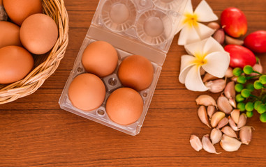 Raw organic brown eggs in package with ingredients on wood table