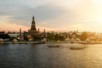 Wat Arun during sunset woth longtail boat in Chao Phraya river a