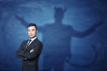 Businessman standing with hands across and his shadow on blue blackboard behind him tail like devil