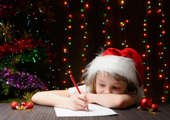 Girl wrote in red pencil a letter to Santa Claus