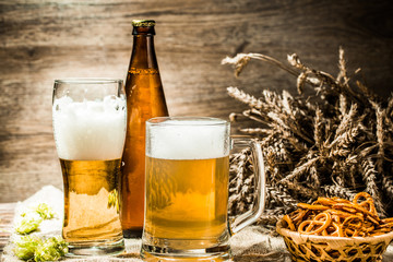 Mug, glasse, bottle of beer with foam on wooden table