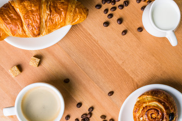 Coffee cup with milk jug, cinnabon and croissant on wooden background.