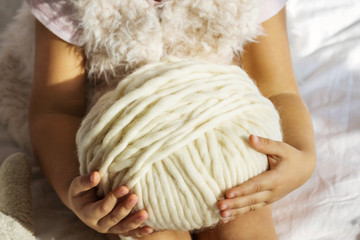 little girl sitting in the bedroom on a bed and holding a large ball of yarn from alpaca