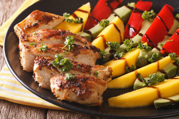 Salad with grilled chicken, mango, avocado and pepper close-up. horizontal