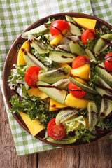 salad of mango, avocado, kiwi, lettuce, tomato dressed with balsamic sauce closeup. vertical top view